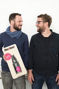 Die beiden Jungs von Vakant-Design mit der von ihnen designten Pfandbon-Sammelbox. Foto: Lena Maja Wöhler.